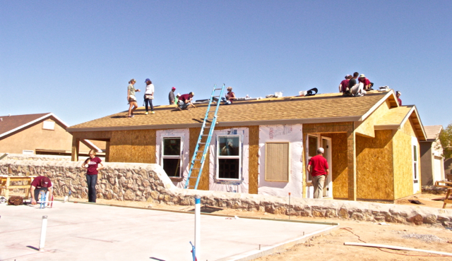 Students from NMSU (New Mexico State University) Civil Engineering Dept. putting shingles on the roof