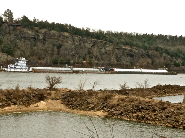 Barge being pushed along by a Tugboat after descending thru the Lock.